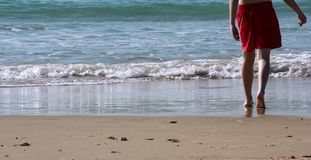 Legs of a teenager running to the sea water royalty free stock image
