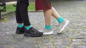 Legs of teens, girlfriend coming to boyfriend with flowers, standing on tiptoes. Stock footage stock video footage