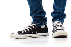 Legs with tennis shoes and jeans. On a white backgroud stock photos