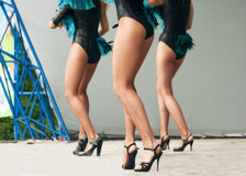 Legs of three girls dancing on stage. Outside on summer day stock photography