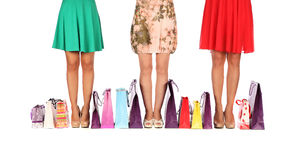 Legs of three glamorous girlfriends with paperbags Stock Image
