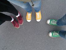 Legs top view. Legs of three people in red, green and yellow gumshoes and black and denim jeans top view Stock Images