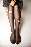 Legs with torn pantyhose. Pair of legs with torn black pantyhose stock photography