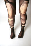 Legs with torn pantyhose Royalty Free Stock Images