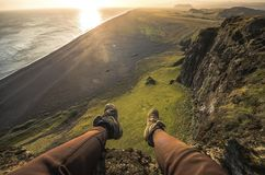 Legs of tourist in tracking shoes and view of Black sand beach in Iceland Stock Photography