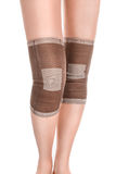 Legs with tourmaline knee pads. Closeup of woman legs with two compression knee braces isolated on white stock photos