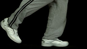 Legs in tracksuit running against black background Royalty Free Stock Photo