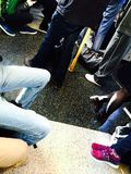 Legs on a train. People standing and sitting on the London Royalty Free Stock Images