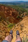 Legs of traveler with mountain boots in Badlands of Ponton de la Oliva, Madrid, Spain royalty free stock photo