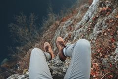 Legs of traveler sitting on amountain top in travel Stock Photo