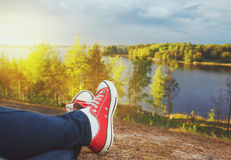 Legs of traveler sitting on the cliff. Travel and freedom concep Stock Photo