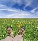 Legs of traveler on green meadow Royalty Free Stock Image