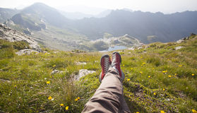 Legs of traveler sitting on a peak. Freedom concept Stock Images