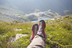 Legs of traveler sitting on a peak. Freedom concept Royalty Free Stock Photography