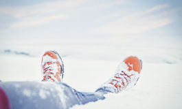 Legs of traveler sitting in snow. Travel and discovery concept Royalty Free Stock Photo