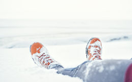 Legs of traveler sitting in snow. Travel and discovery concept Royalty Free Stock Image
