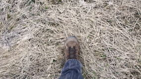 Legs in trekking boots walking on withered grass, above view stock video footage