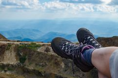 Legs in trekking shoes. With mountain landscape in a background royalty free stock photography