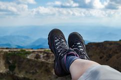 Legs in trekking shoes. Resting on a mountain field stock photo