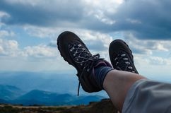 Legs in trekking shoes. With mountain landscape in a background royalty free stock photos