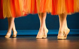Legs of a trio of ballet dancers in red and yellow skirts. In front of dark blue curtain Royalty Free Stock Photos