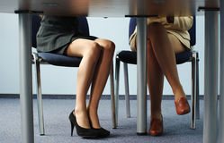 Legs of two businesswomen under. The meeting room table Royalty Free Stock Images