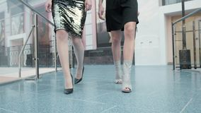Legs of two girls in fashion dresses walking with bags in shopping center, close up girls on high heels. Legs of two girls in dresses standing with bags in stock footage