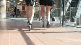 Legs of two girls in fashion dresses walking with bags in shopping center, close up girls on high heels. Legs of two girls in dresses standing with bags in stock video
