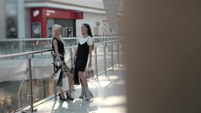 Legs of two girls in fashion dresses walking with bags in shopping center, close up girls on high heels Stock Photos