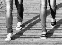 The legs of two girls in jeans and comfortable shoes while walking / Black and white photo. In a retro style royalty free stock photography