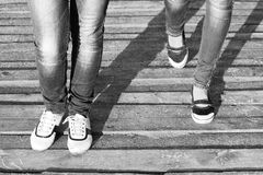 The legs of two girls in jeans and comfortable shoes while walking / Black and white photo Royalty Free Stock Photo