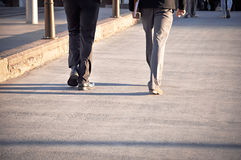 Legs of two men walking on the pavement Stock Photo