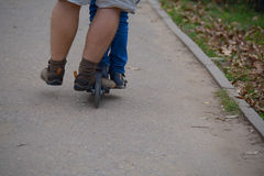 Legs of two people on one scooter Royalty Free Stock Images