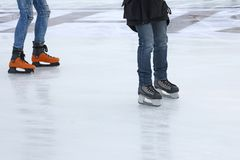 Legs of two people skating on the ice rink Stock Image
