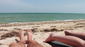 The legs of two people are sunbathe on the beach stock video