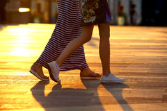 Legs of two people walking on the background of sunlight. The legs of two people walking on the background of sunlight Royalty Free Stock Photo