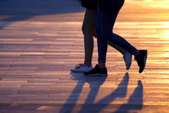 Legs of two people walking on the background of sunlight. The legs of two people walking on the background of sunlight Royalty Free Stock Images