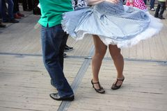 Legs of two rock`n roll dancers. In green shirt, blue jeans and light blue skirt  on wooden floor Royalty Free Stock Photo