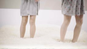 Two unrecognizable girls in dresses jumping on a king size bed. Legs of two unrecognizable girls preschoolers or school students wearing dresses jumping on their stock video footage