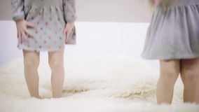 Two unrecognizable girls in dresses jumping on a big bed. Legs of two unrecognizable girls wearing dresses jumping on a large bed with a fur like cover. Concept stock video footage