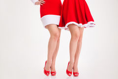 Legs of two women in santa dresses and red shoes Stock Photography