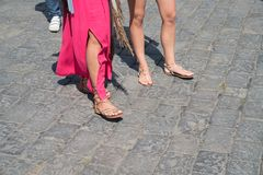 Legs of two women walking. Feet blurred in motion one red dress Royalty Free Stock Photo