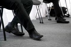 The legs of the unemployed, waiting for their turn for an interview, sitting on office chairs in the hallway. Unemployment and job stock photos