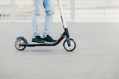 Legs of unknown male in black sneakers and jeans rides on electric scooter over urban asphalt, enjoys sunny day. People and leisur. E time concept stock image