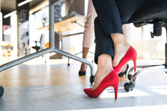 Legs of unregognizable business women in high heels. Close up of legs of unregognizable business women in high heels in the office royalty free stock photography