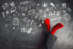 Legs up the wall, putting feet up. Man wearing red socks in relaxing yoga pose with his legs on the wall and various doodle icons for fun and enjoyment Stock Photos