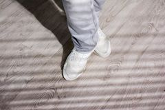 Legs of urban rap dancer. Guy in jeans and white sneakers dancing on studio background. Modern style young dancer, cropped image Royalty Free Stock Photo