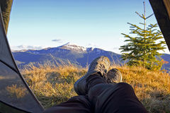 Legs vacationer camper in tent with mountain view Royalty Free Stock Photos