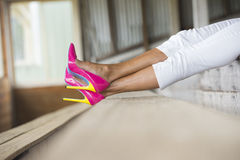 Legs and very high heels lying relaxed. Concept close up image of woman lying in Elegant sexy pink high heel shoes, relaxed on bench, copy space, blurred Stock Photo