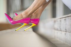 Legs and very high heels sitting relaxed. Detail Concept close up image of woman standing in Elegant sexy pink high heel shoes, relaxed on bench, copy space Royalty Free Stock Photos